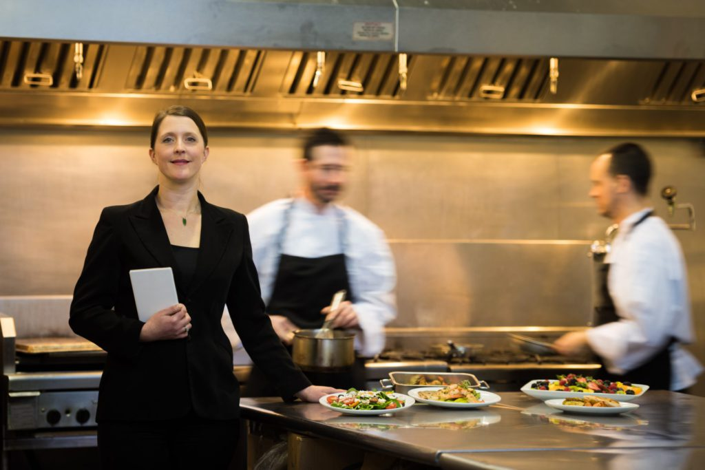 Business woman standing in a restaurant kitchen with two chefs working behind her and plating food.