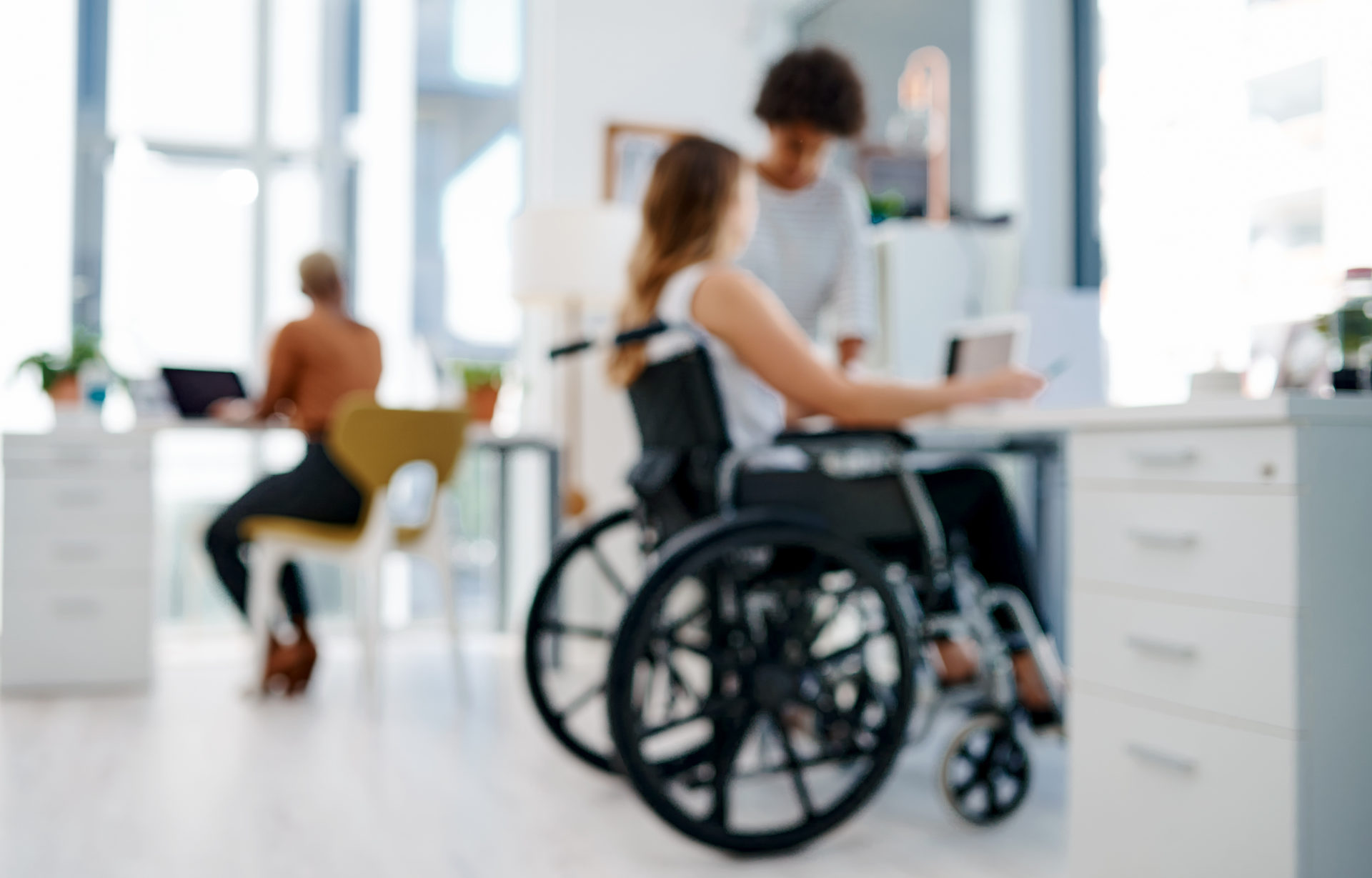 Picture of a f a business woman in a wheel chair working with colleagues in a modern office