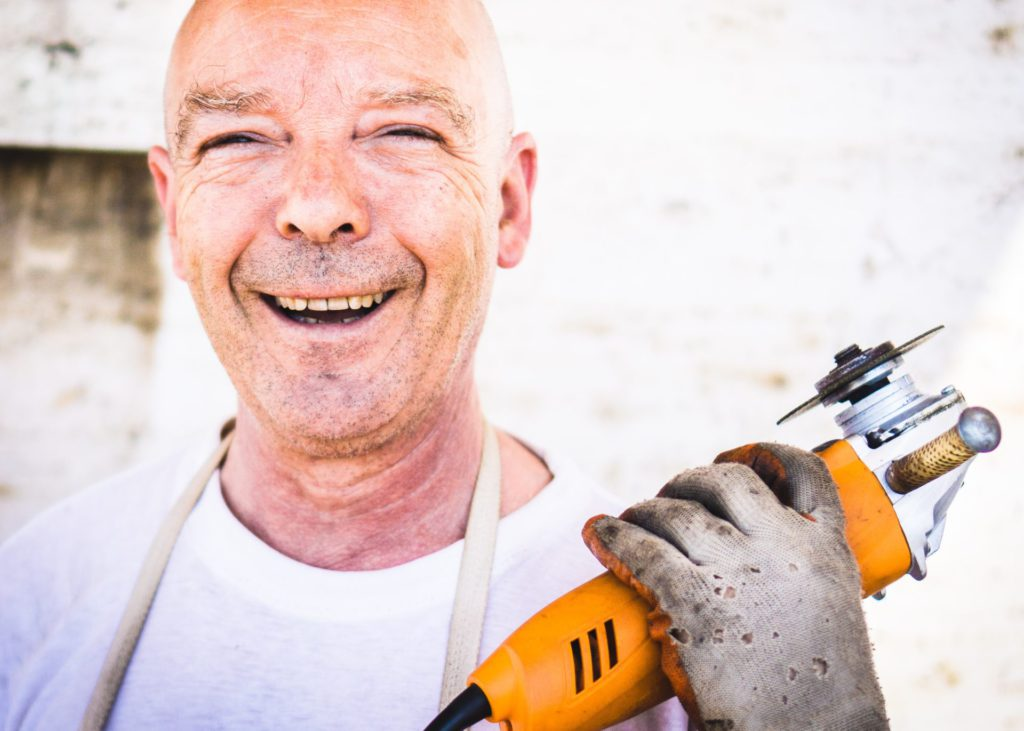 Older male worker with power tool in his hand and is smiling.