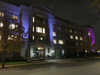 Picture of a large office building with purple spotlights shining on the building.